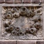 Gevelsteen DE ROSE KRANS Montelbaansstraat 6 Amsterdam. In de zijgevels van het, in de jaren '25 gebouwde verenigingsgebouw zijn twee gevelstenen ingemetseld, afkomstig uit gesaneerde panden in de buurt. De steen met de bloemenkrans is afkomstig van Ridderstraat 54.